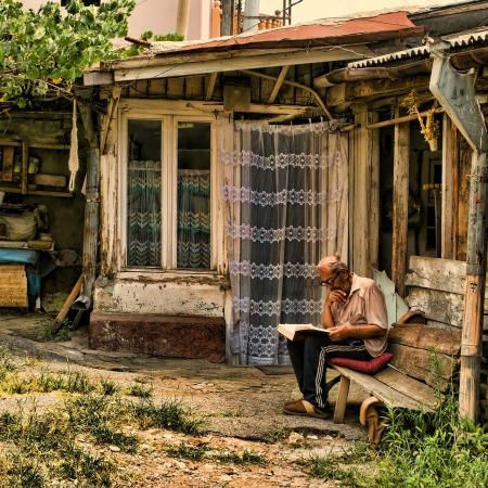 Old man in garden reading